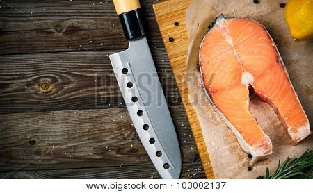 Fresh and raw steak salmon on wooden cutting board with rosemary and pepper