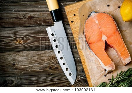 Fresh and raw steaks trout on wooden cutting board with rosemary and pepper