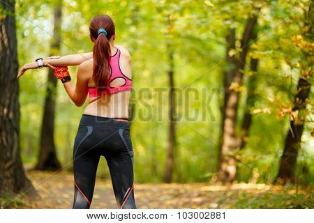 attractive woman runner stretching before her workout in park