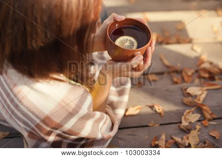warm cup of hot coffee warming in the hands of a girl, autumn outdoors