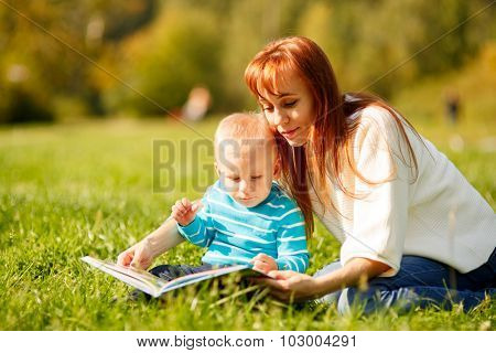 Mother with son reading book in park