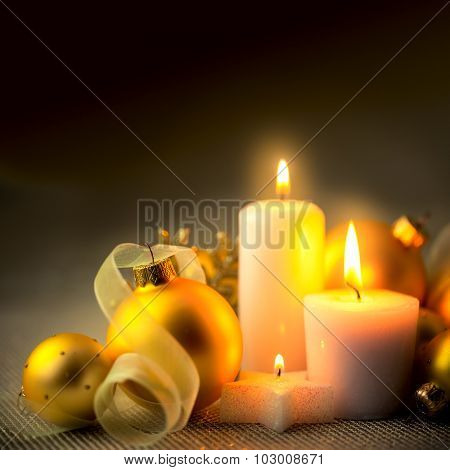 Evening Christmas Decorations background with candles, baubles and ribbons - copy space for text