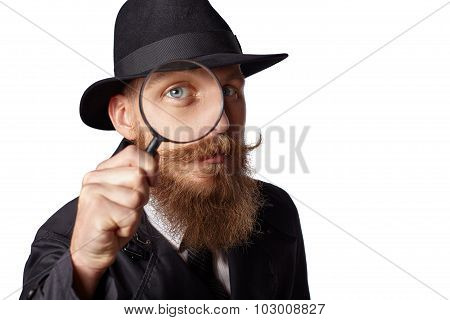 Bearded man looking through a magnifying glass.