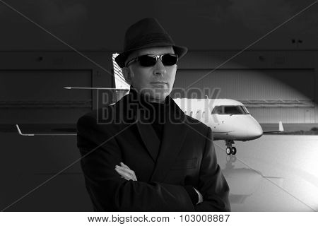 Business man standing next to private jet