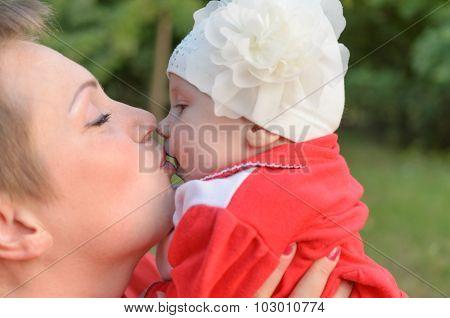 Loving mother tenderly kissing her child.