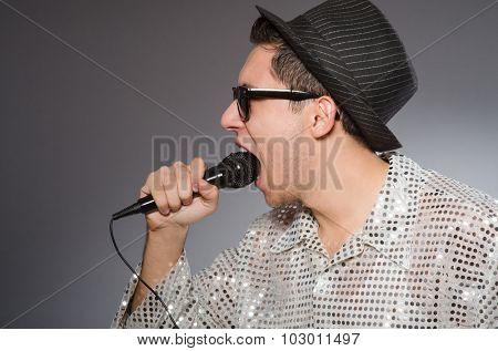 Young cheerful singer with microphone