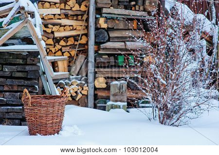 basket with fire wood neat wood shed in snowy winter garden