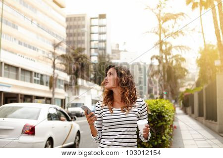 Young Lady Walking On City Street And Looking Away