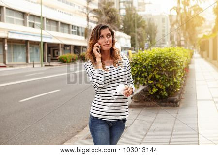 Young Woman Speaking On Mobile Phone While Walking
