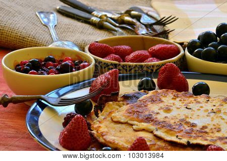 Yummy crepes with strawberries and huckleberries on wooden background