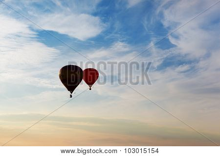 Silhouettes of couple flying balloons on the sunset sky