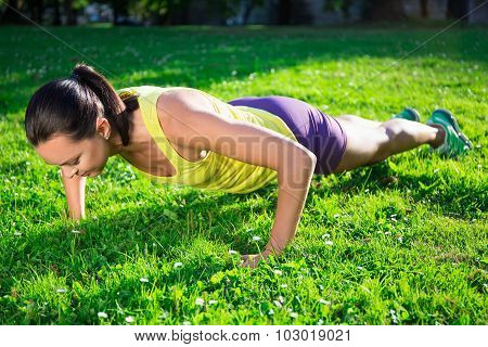 Beautiful Woman Doing Push Up Exercise In Park