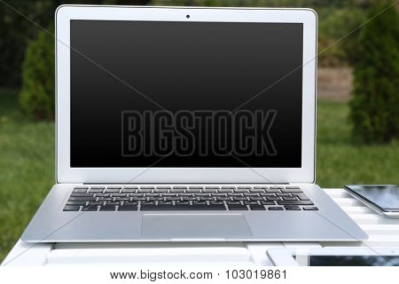 Laptop and papers on wooden table outdoor