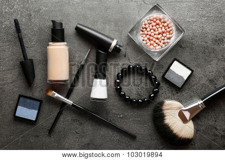 Different cosmetics on dark grey background