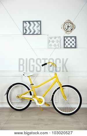 Yellow retro bicycle in spacious bright room
