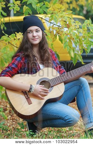 Portrait of acoustic guitar female player travelling by yellow van at autumn leaves background