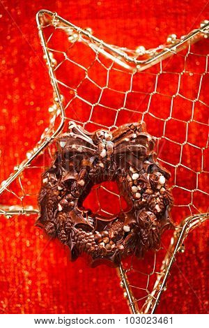 festive christmas wreath - dark chocolate with nuts and rice crisps on red golden background
