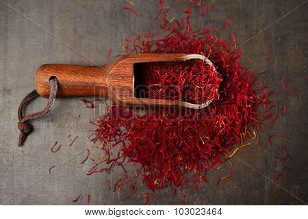 saffron spice threads   in vintage  old scoop,  old metal background, closeup
