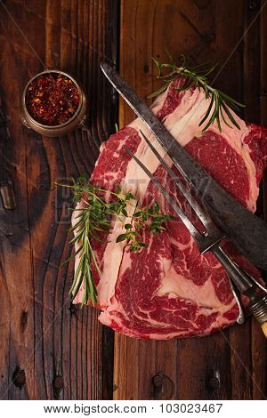 raw beef Ribeye  steak   on wooden  table with vintage carving fork , knife and spices
