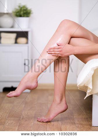 Legs Of Woman Applying Cream On It