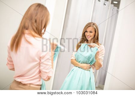 Young girl at the mirror in the store