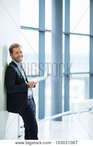 Smiling businessman with a laptop at the airport