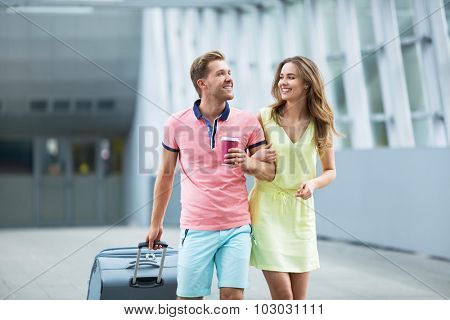 Young couple with a suitcase at the airport
