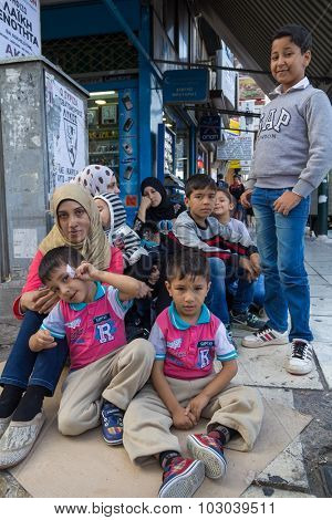 PIRAEUS, GREECE: SEPTEMBER 19, 2015: Family of immigrants and refugees from Middle East and North Africa sitting at the cardboard box at street.