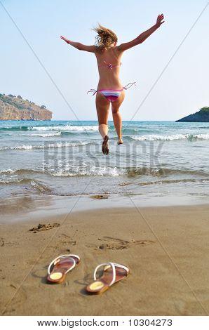 Excitada mujer corre hacia el mar