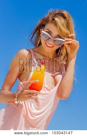 outdoor portrait of young smiling beautiful woman with bright cocktail isolated over blue sky background