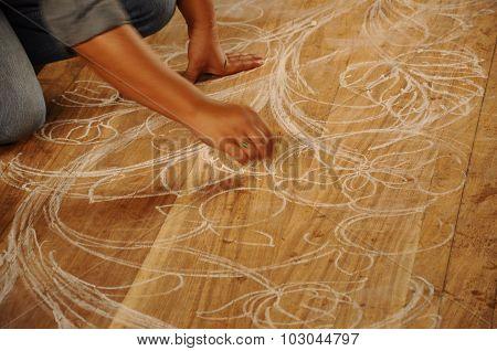 Skilled craftsman sketches carving design on wood before start carving work