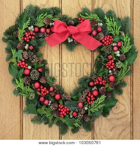Christmas heart shaped wreath with red baubles and bow, holly, mistletoe and winter greenery over oak front door background.