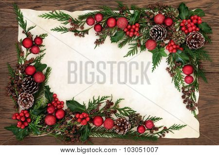 Christmas background border with red bauble decorations, holly, ivy, fir and cedar cypress greenery on parchment paper over old oak wood.