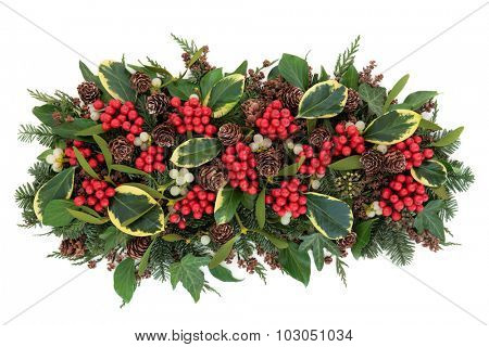 Christmas and winter flora with variegated holly, mistletoe, ivy, pine cones and traditional greenery over white background.