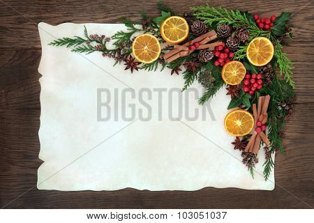 Christmas abstract background border with dried fruit and spice, holly, ivy, cedar cypress and fir on parchment paper over old oak wood.