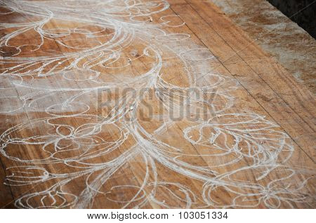 Skilled craftsman sketches carving design on wood before start carving work