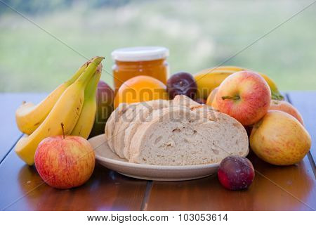 variety of fruits and bread on table in the garden
