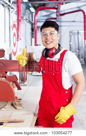 Proud worker at his workplace in Asian industrial plant next to a production machine