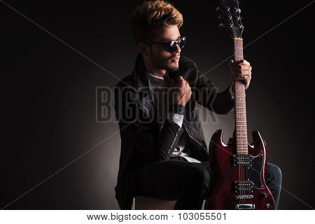 side view of a cool guitarist sitting and holding his electric guitar , looking away from the camera on black studio background