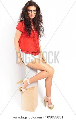 surprised smart beautiful woman sitting on a chair in studio while touching one leg and raising the other one
