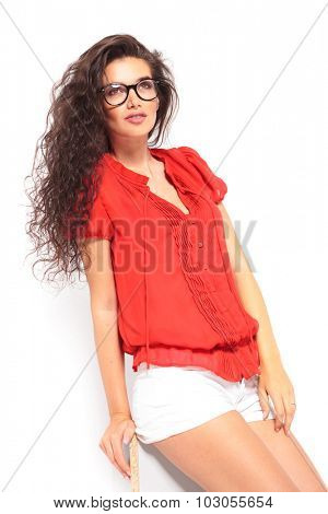 smiling sensual girl wearing glasses and leaning against the wall while looking up