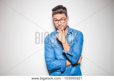 handsome man leaning against the wall, touching his chin while wearing denim shirt and glasses