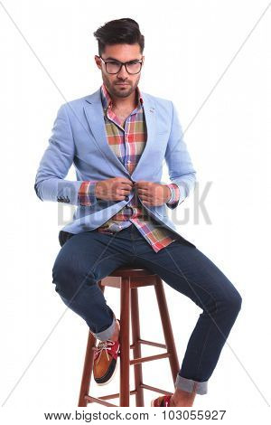 Handsome casual man closing his jacket while sitting on a chiar.