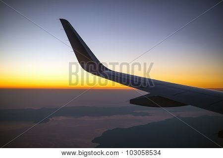 Wing Of An Airplane At Sunset, View From Window.