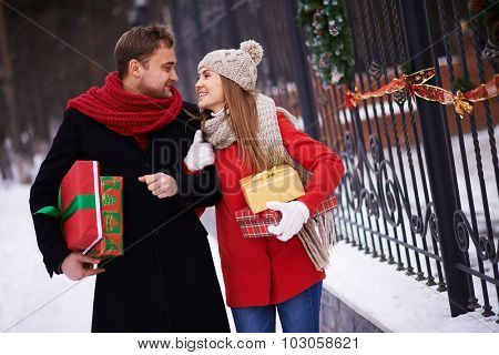 Young couple with giftboxes looking at one another while moving outdoors on Christmas eve