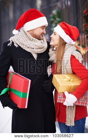 Amorous couple in Santa caps and coats holding presents for Christmas