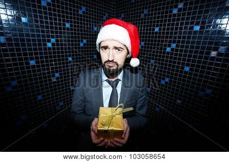 Dissatisfied businessman with giftbox looking at camera in night club