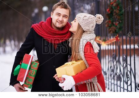 Young woman with giftboxes saying something to her husband outdoors on Christmas eve