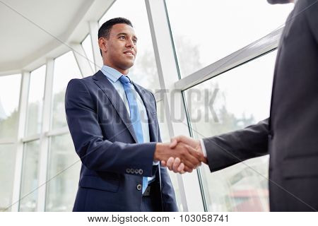Confident businessman greeting his partner in office