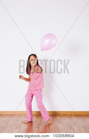 Little girl holding color balloon with gray background
